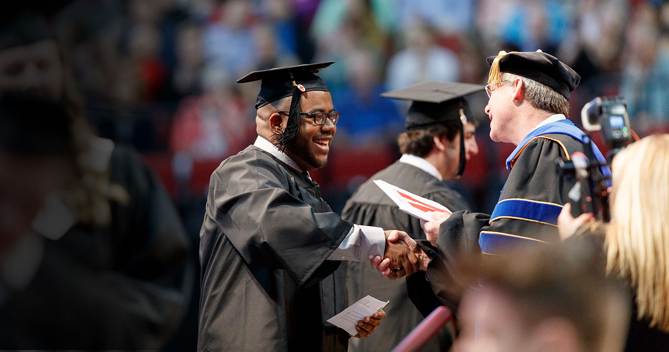 smiling graduating student shakes professors hand after receiving his diploma